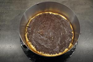 18) Tortenring umstellen, den 1. Biskuit auflegen und mit Kuvertüre bestreichen