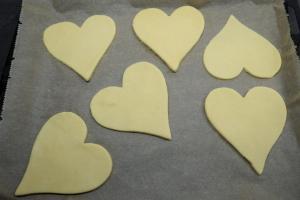 3) Die Herzen auf ein Backblech mit Backpapier legen. Kurz ins Gefrierfach legen