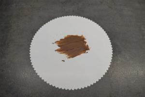9) Etwas Ganache oder Nutella auf einem Cakeboard verteilen