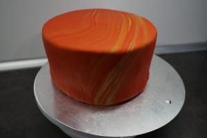 21) Fondant vermischen, ausrollen und über die Torte geben, glatt streichen