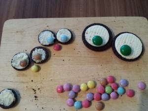 14) Smarties und mini Smarties mit etwas Kuvertüre auf die Oreo Kekse kleben