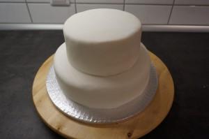 16) Die kleine Torte darauf stellen und andrücken. Einen Stab in der Höhe der Torte von oben durch die Torte stechen
