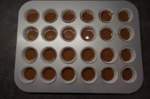 2) Schokolade schmelzen und ca. 1-1.5 TL in jedes Förmchen geben. Kühl stellen.