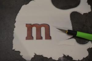 10) Das M&M Logo ausdrucken und zuschneiden und auf dem weißen Fondant legen