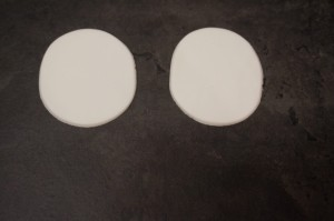 9) Zwei große und zwei sehr kleine Kreise aus weißem Fondant ausschneiden, 2 kleine aus schwarzem Fondant ausstechen