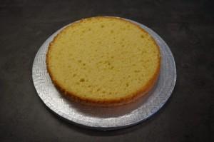 3) Untersten großen Boden auf ein Cakeboard geben. Tortenring darum stellen