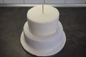 22) Kleinere Torte auflegen und mit einem langen Stab die Torte in der Mitte fixieren